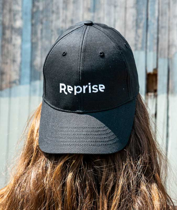 girl wearing backwards black baseball cap from reprise.