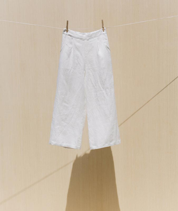 The isamu wide leg pant in ivory linen hanging from a clothesline